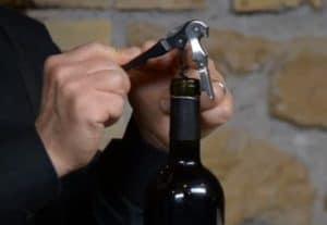 persona abriendo una botella de vino con un sacacorchos