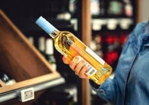persona con una botella de vino blanco