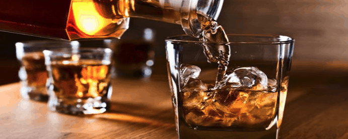 persona sirviendo whisky