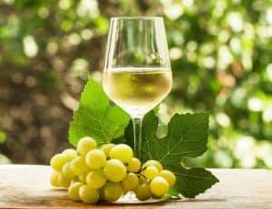 copa de vino blanco y uvas