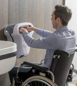 hombre en silla de ruedas usando un secamanos