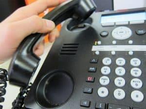 persona cogiendo un teléfono fijo