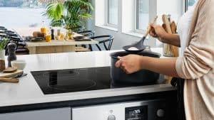 mujer cocinando en una placa de cocción