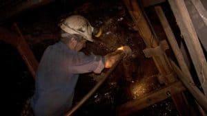 persona en la mina usando una lámpara frontal