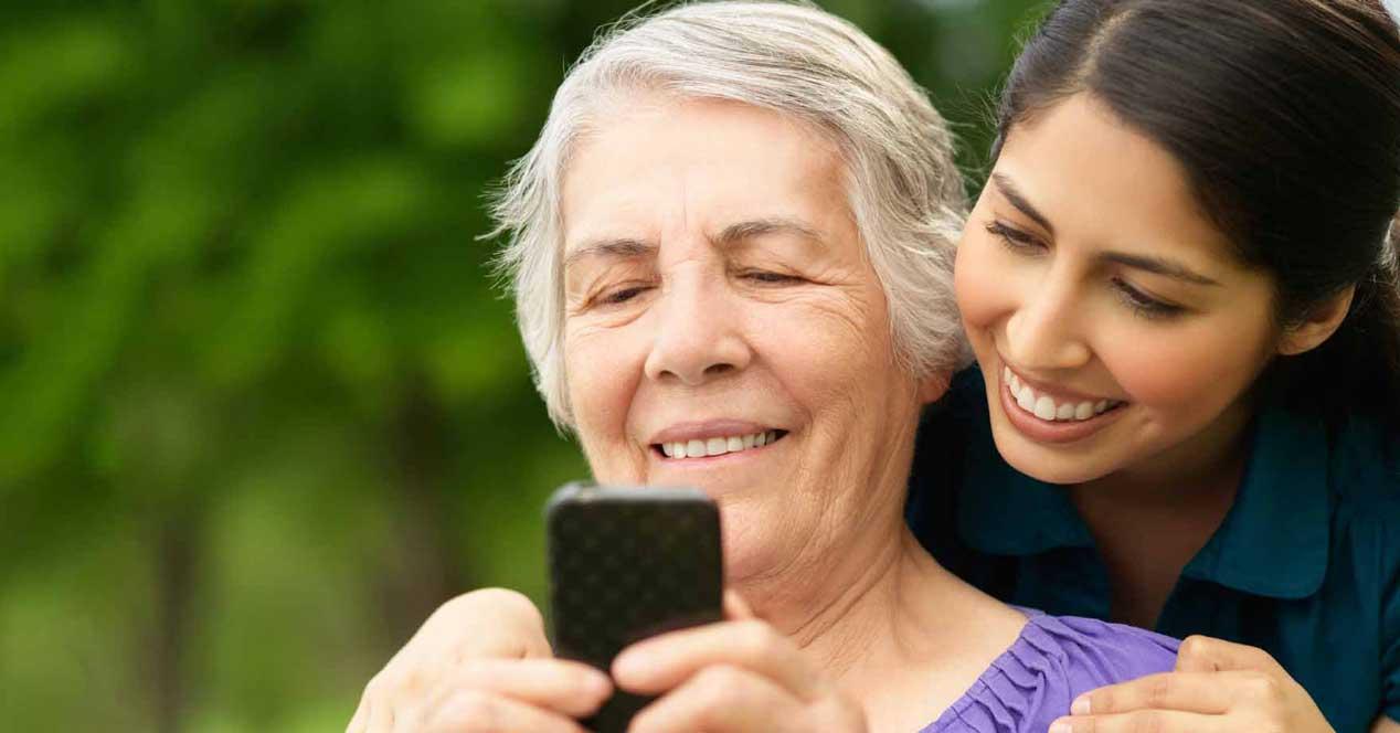 madre e hija con móvil para personas mayores