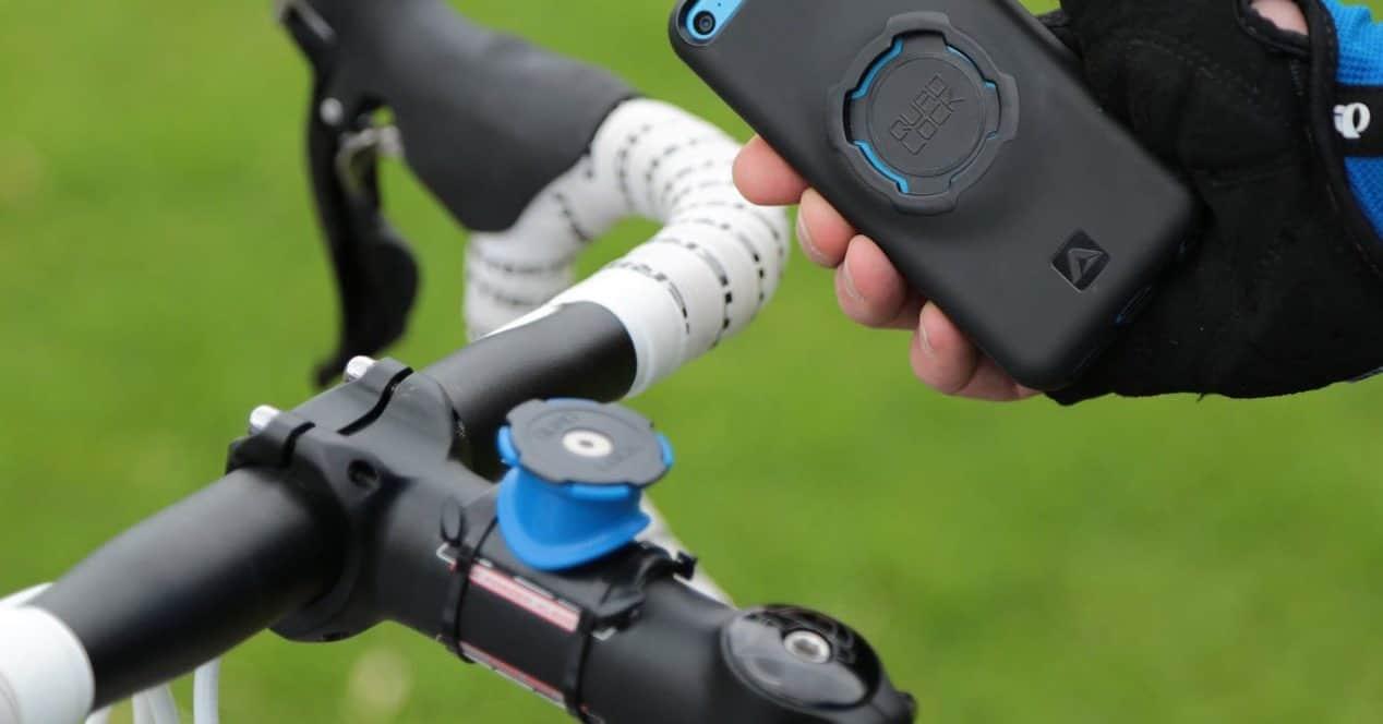 persona poniendo móvil en un soporte para bici