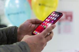 persona con un teléfono móvil rojo