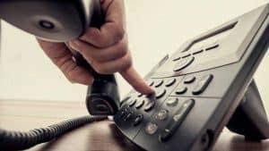 persona marcando un teléfono fijo
