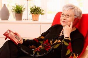 persona mayor usando un teléfono fijo
