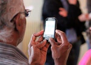señor mirando un móvil para personas mayores