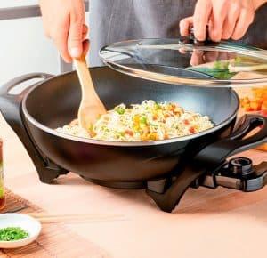 persona cocinando en un wok eléctrico