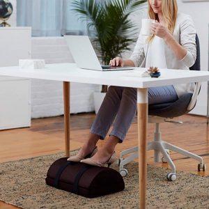 mujer usando un reposapiés de oficina blando