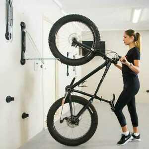 mujer poniendo una bici en un portabicicletas de pared