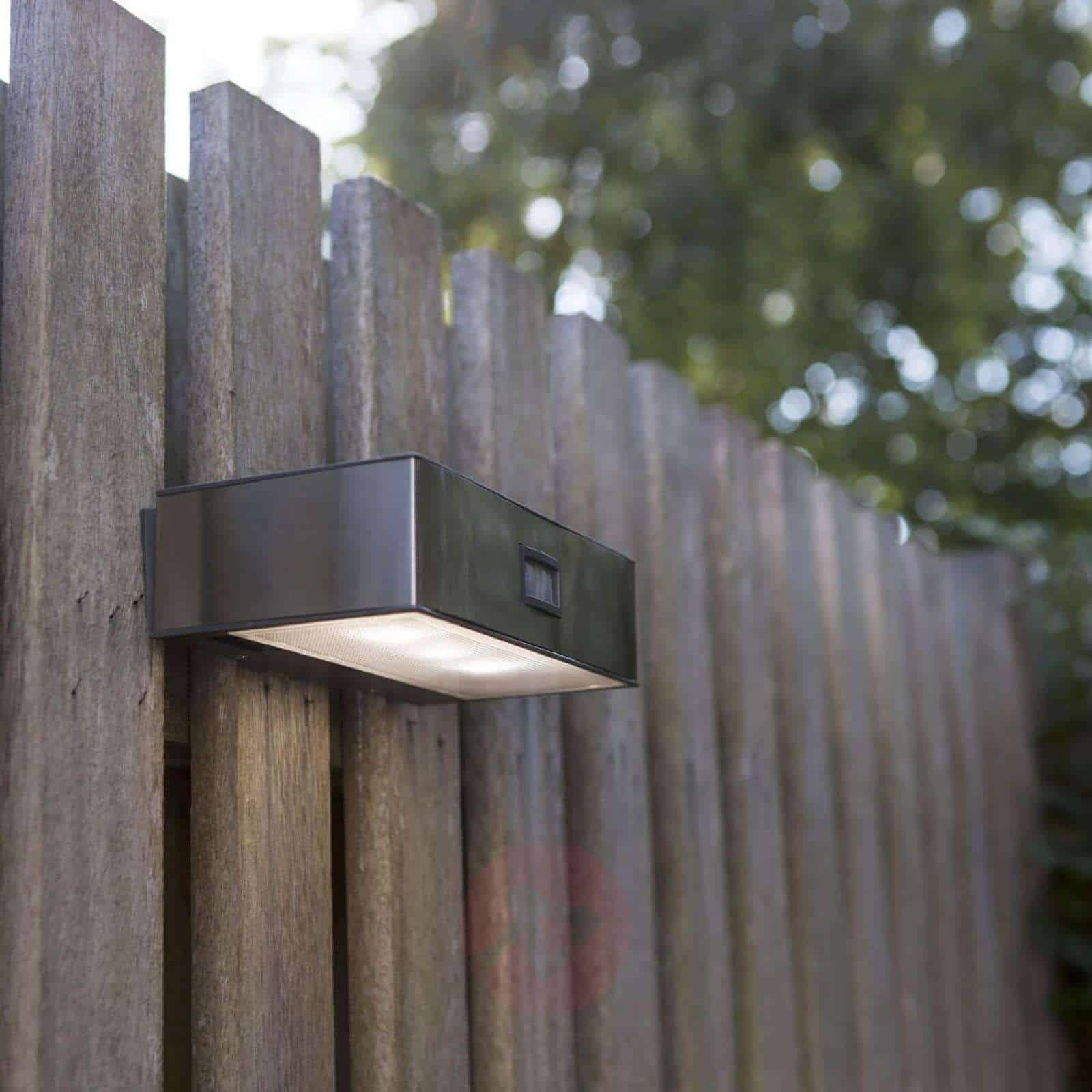 lámpara solar en una valla de madera
