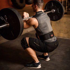 hombre usando un cinturón lumbar en levantamiento de peso