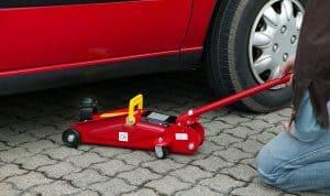 persona colocando un gato hidráulico bajo el coche