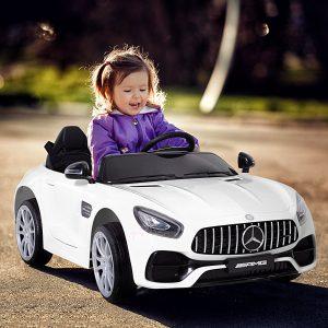 niña en un coche eléctrico para niños mercedes