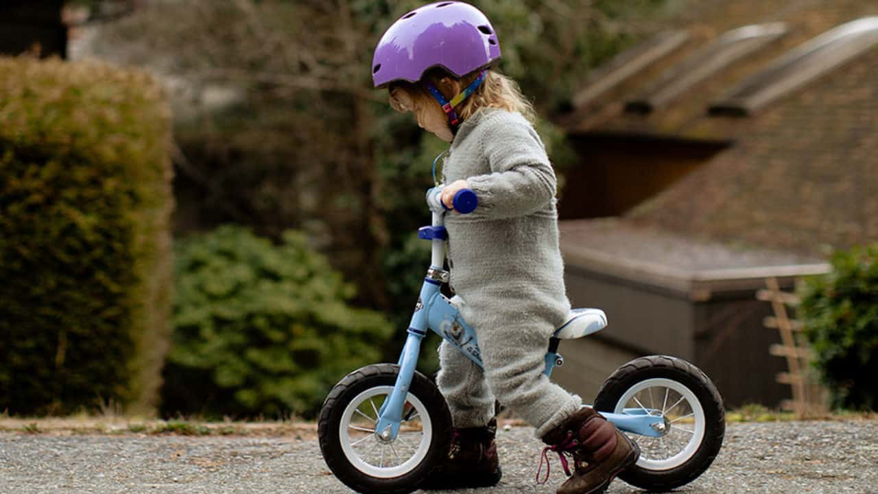 niña pequeña en una bicicleta sin pedales