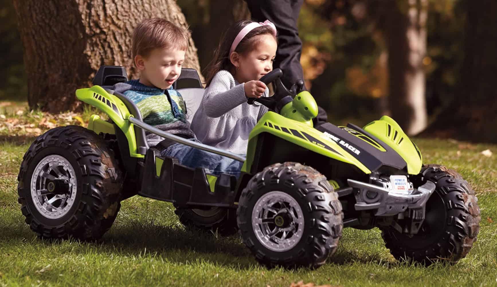 niño y niña en un coche eléctrico para niños
