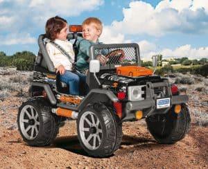 niña y niño en un niño en un coche eléctrico para niños todoterreno