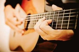 persona tocando una guitarra clásica