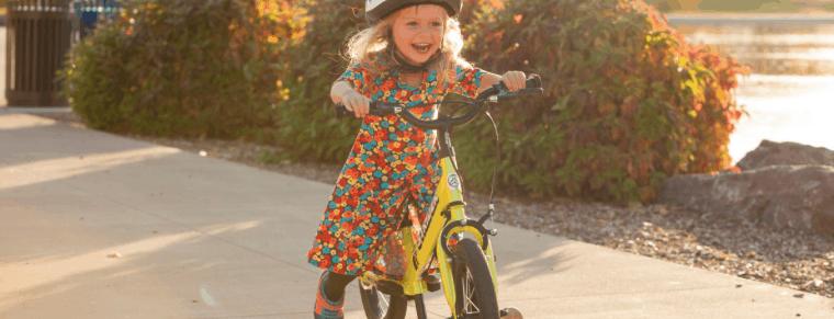 niña en una bicicleta sin pedales amarilla