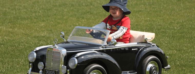 niño con sombrero en un coche eléctrico para niños
