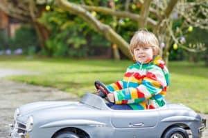 niño en un coche eléctrico para niños gris