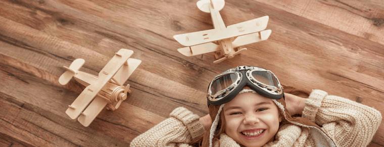 niño con aviones de madera