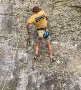 persona escalando con arnés de escalada